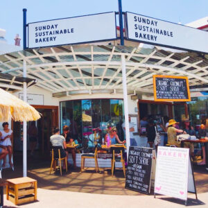 Front Image of Sunday Sustainable Bakery, Byron Bay with people sitting at tables out the front.