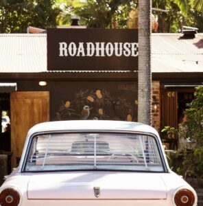 Front image of The Roadhouse, Byron Bay with an old car parked out front