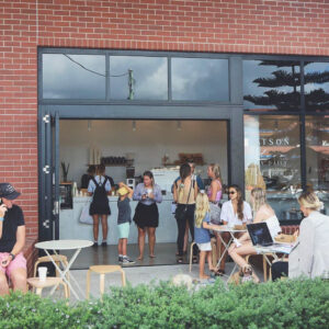 Front image of Watson Bloom Cafe with people sitting at tables out the front