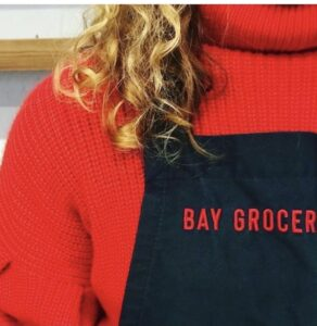 girl wearing red apron from Bay Grocer, Byron Bay