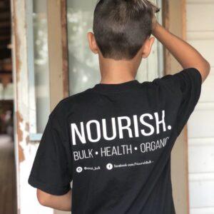 Boy facing door wearing nourish bulk, health, organics t-shirtt